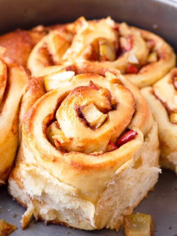 fluffy cinnamon roll with apples on a round pan