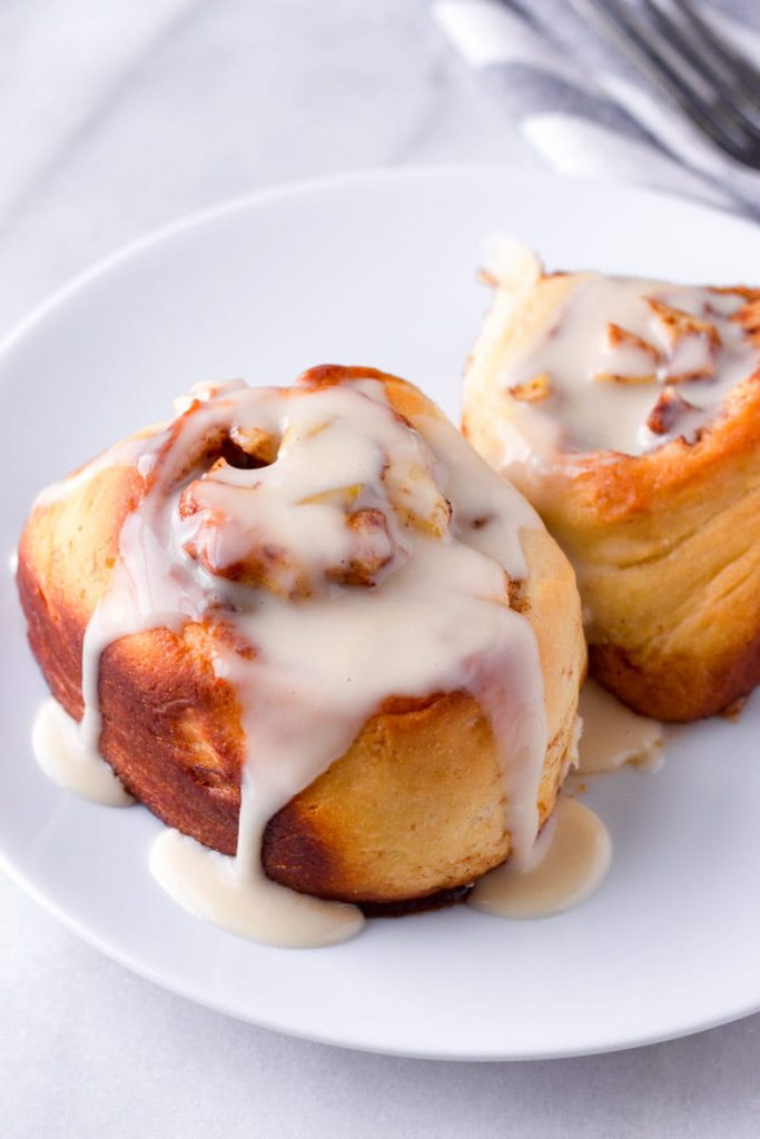 two apple cinnamon buns drizzled with maple icing on a round plate