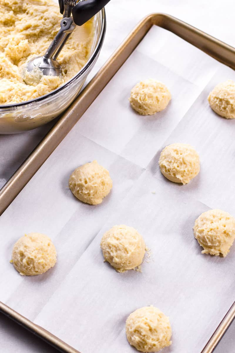 Cookie dough scoops arranged on a sheet pan lined with parchment paper