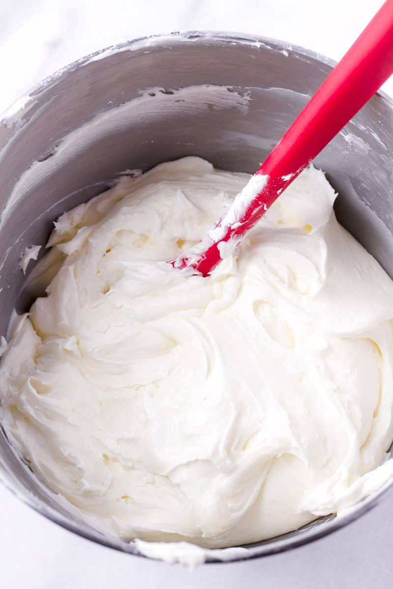 Cream cheese frosting in a mixing bowl with a red silicone spatula