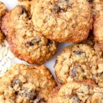 close up of many oatmeal raisin cookies piled up