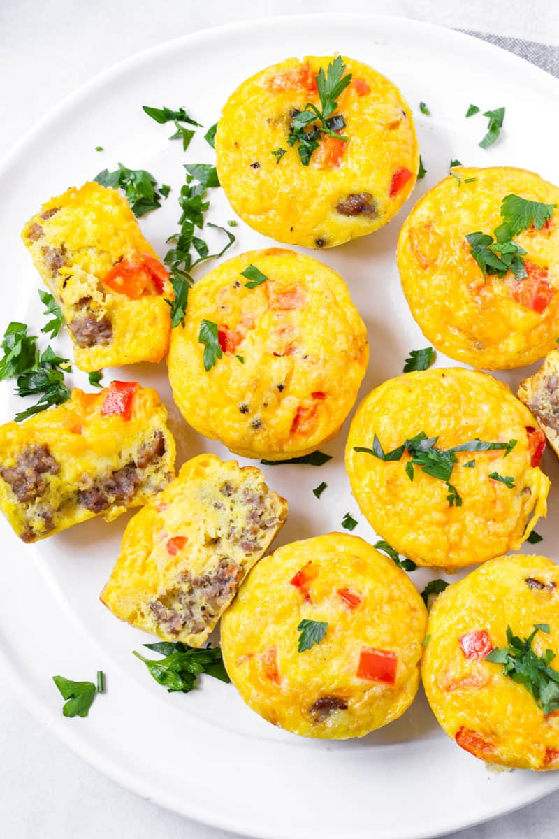 sausage and pepper egg cups arranged on a round plate