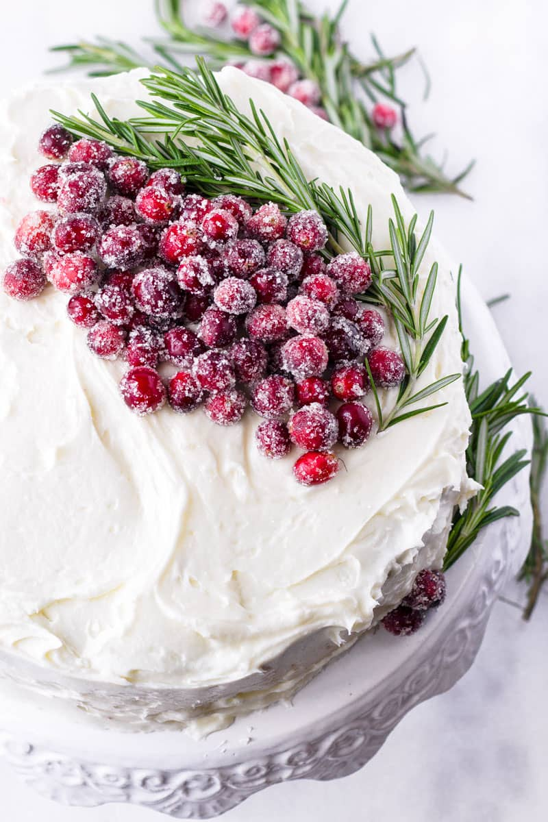 Decorated cake with sugared cranberries and rosemary