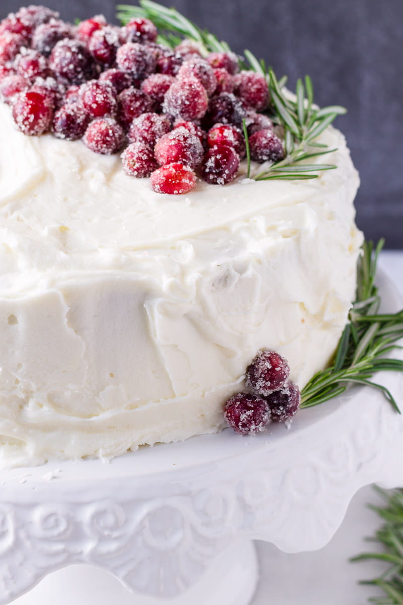 straight shot of cake decorated with sugared cranberries, rosemary, and white frosting