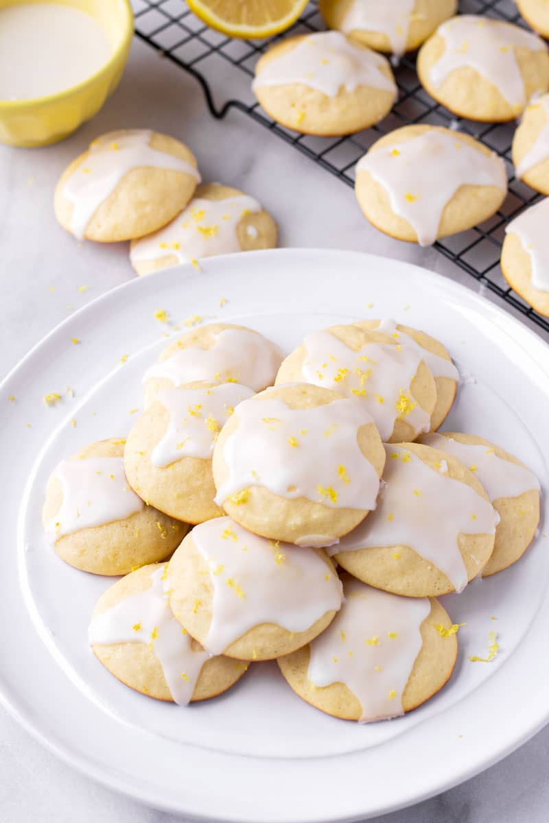 soft lemon cookies on a round white plate plus more cookies cooling on a rack
