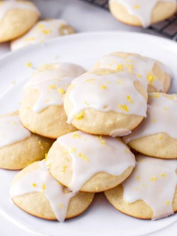 Glazed lemon ricotta cookies with lemon zest piled on a white plate