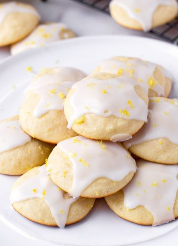 Glazed lemon ricotta cookies with lemon zest piled on a white plate