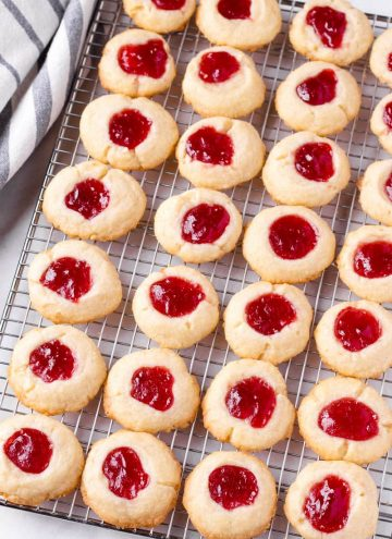 About 28 raspberry butter cookies lined up on a cooling rack