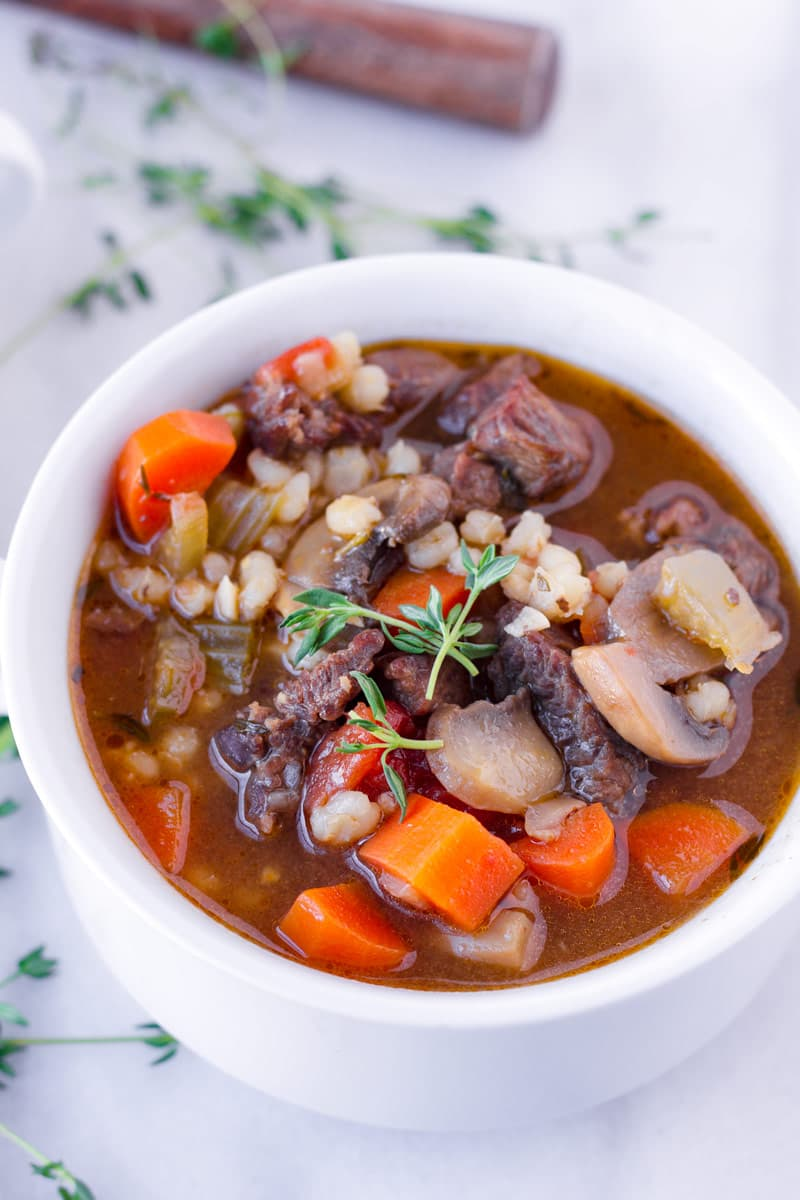 cooked beef and barley soup served in a ceramic bowl