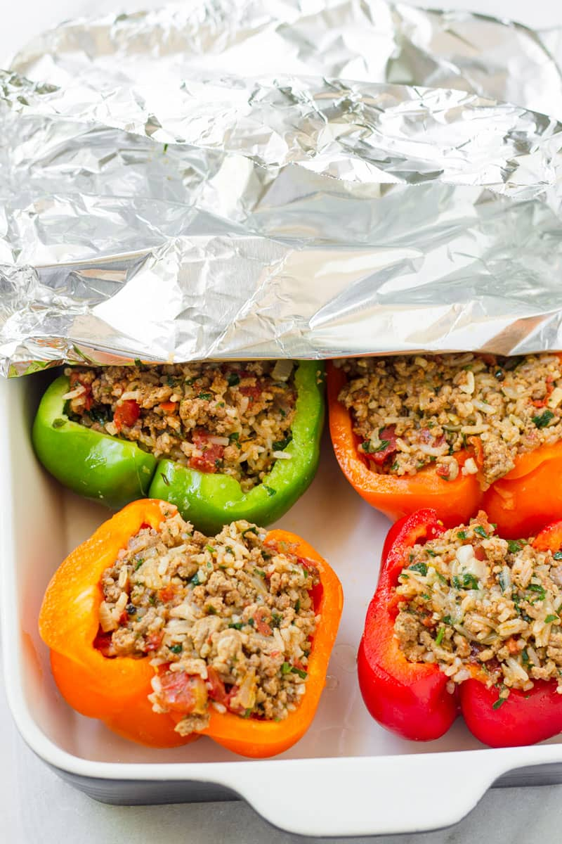 uncooked stuffed peppers in a baking dish, half covered with aluminum foil