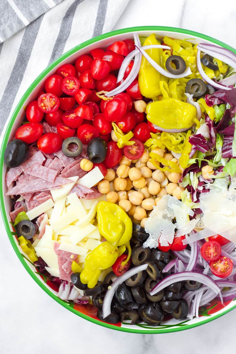 Ingredients for Italian chopped salad arranged in a large round serving bowl