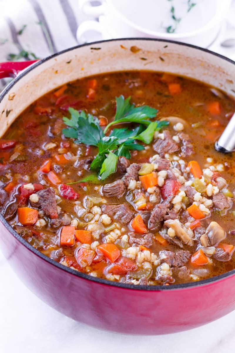 hearty soup in a red dutch oven with italian parsley garnish
