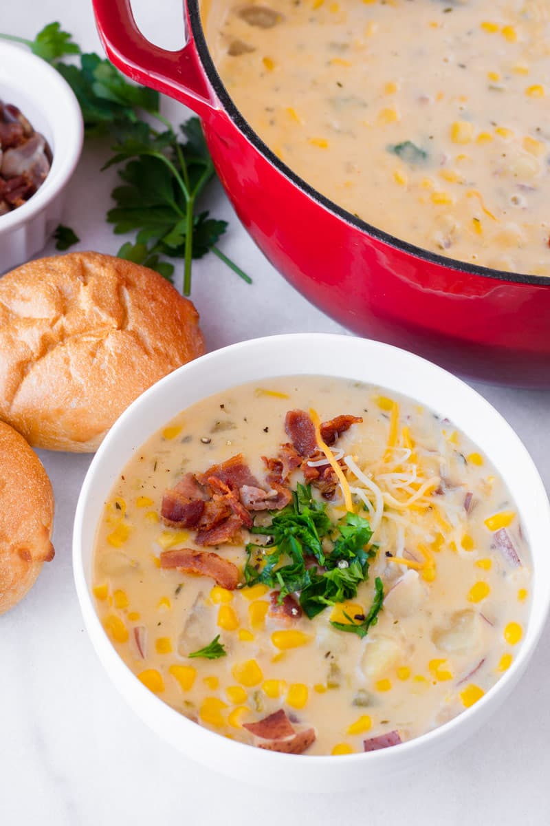 A red Dutch oven and a white ceramic bowl with potato corn chowder