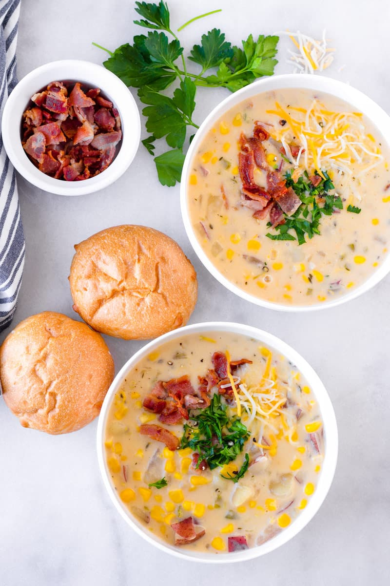 Top view of two bowls of potato corn chowder, two bread rolls, and bacon bits
