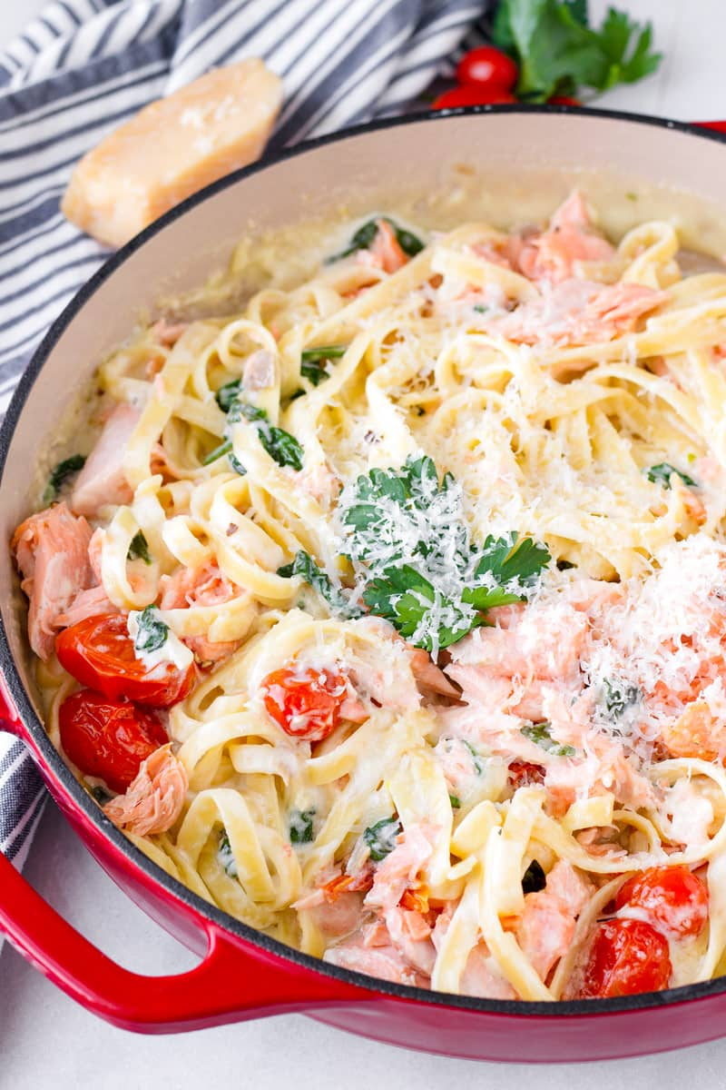 salmon pasta tossed with tomatoes, spinach, cheese, and creamy sauce in a red cast iron pan