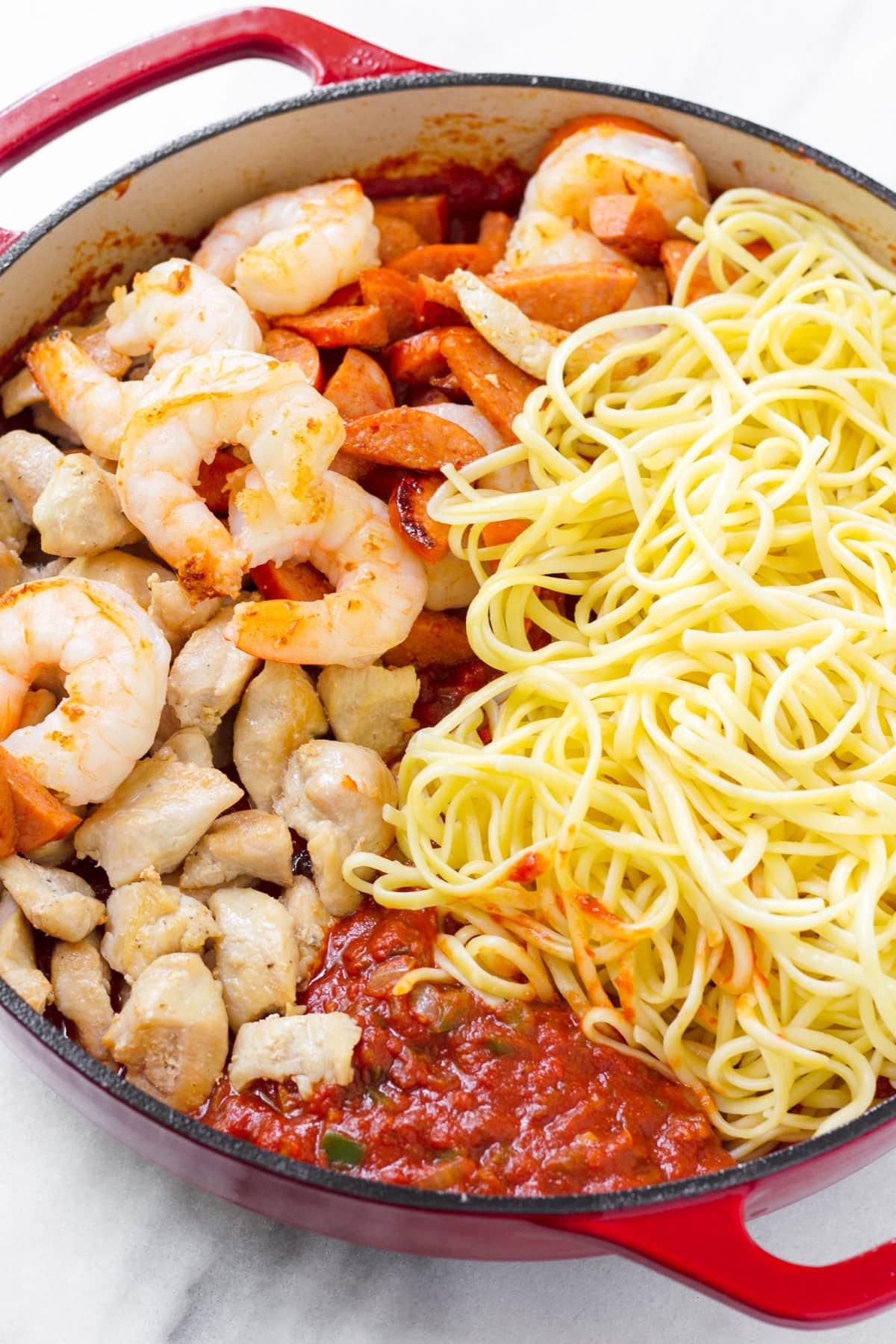 jambalaya pasta ingredients arranged in a pot, including chicken, shrimp, sausage, sauce, and pasta