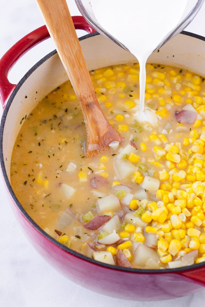 heavy cream being poured into a pot with corn, broth, and vegetables