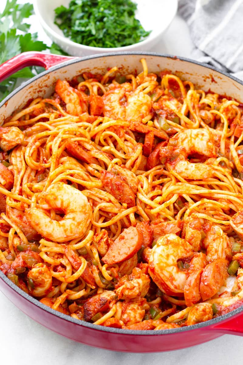 jambalaya linguini made with andouille sausage, shrimp, and chicken in a red Dutch oven