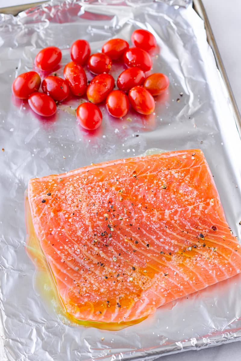 a raw filet of seasoned salmon and grape tomatoes on a lined sheet pan