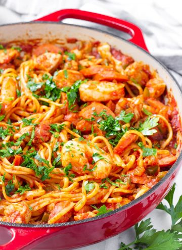 garnished jambalaya pasta dish in a red Dutch oven pot plus parsley garnish