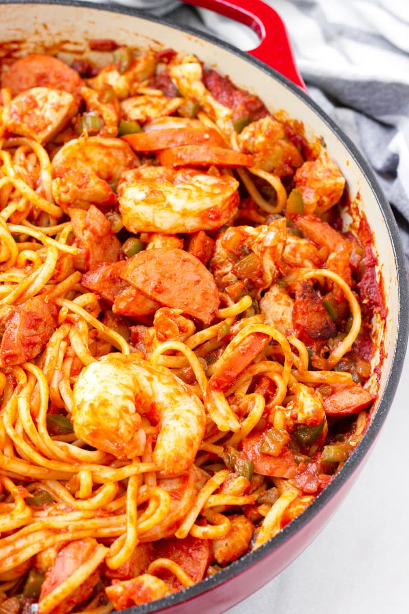 close up of creole inspired linguini in a red Dutch oven pot
