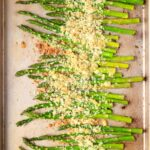 sheet pan with prepared asparagus and breadcrumb cheese topping