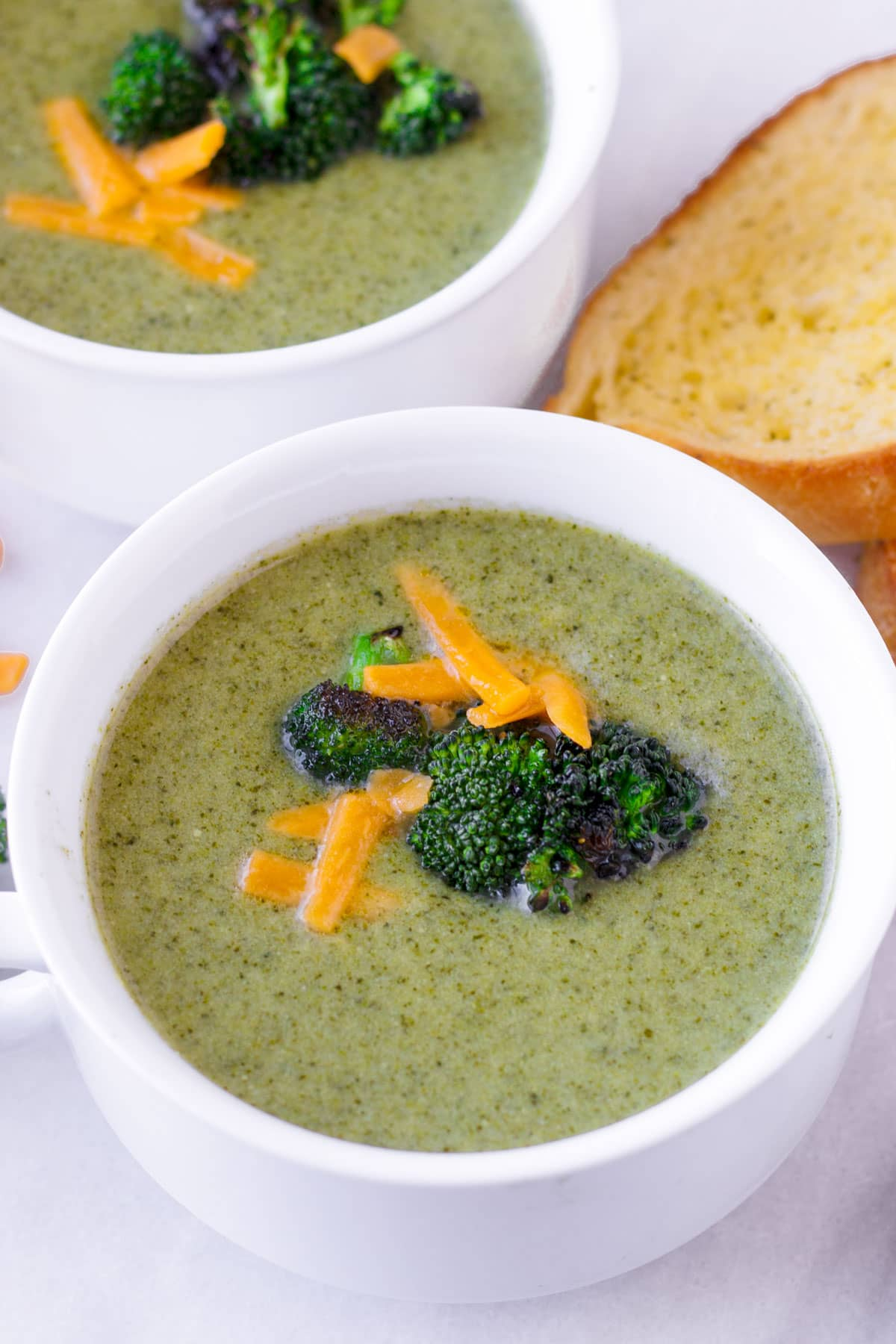 close up of cream of broccoli soup in white ceramic bowls with garmish