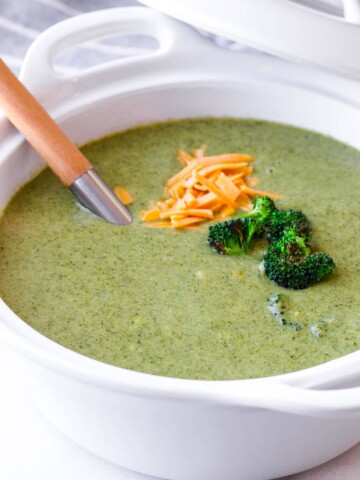 healthy kale and broccoli soup with garnish in a large serving pot and a serving ladle