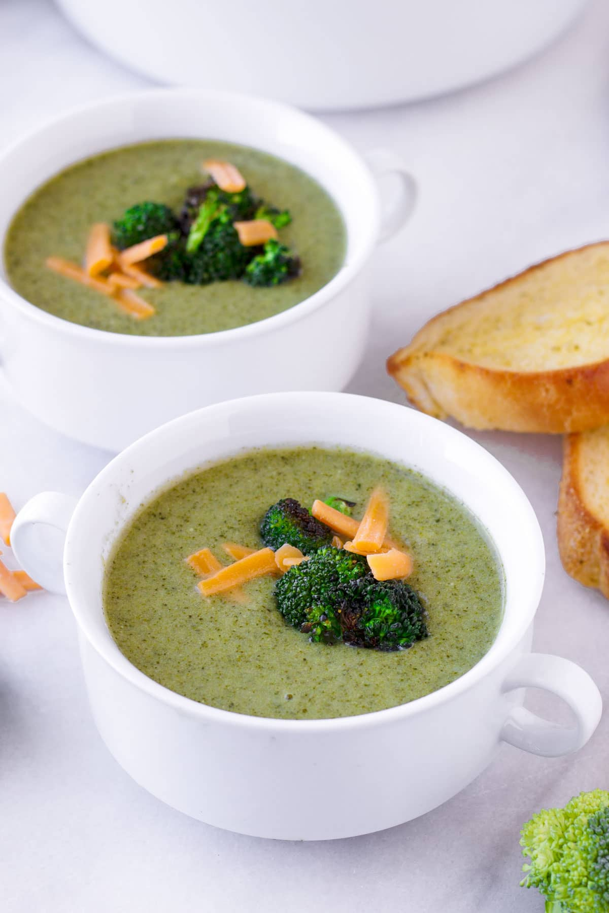 two white ceramic bowls of fresh kale and broccoli creamy soup
