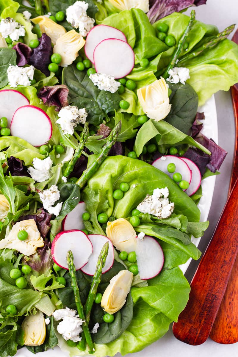 Green salad made with asparagus, peas, greens, artichokes, goat cheese