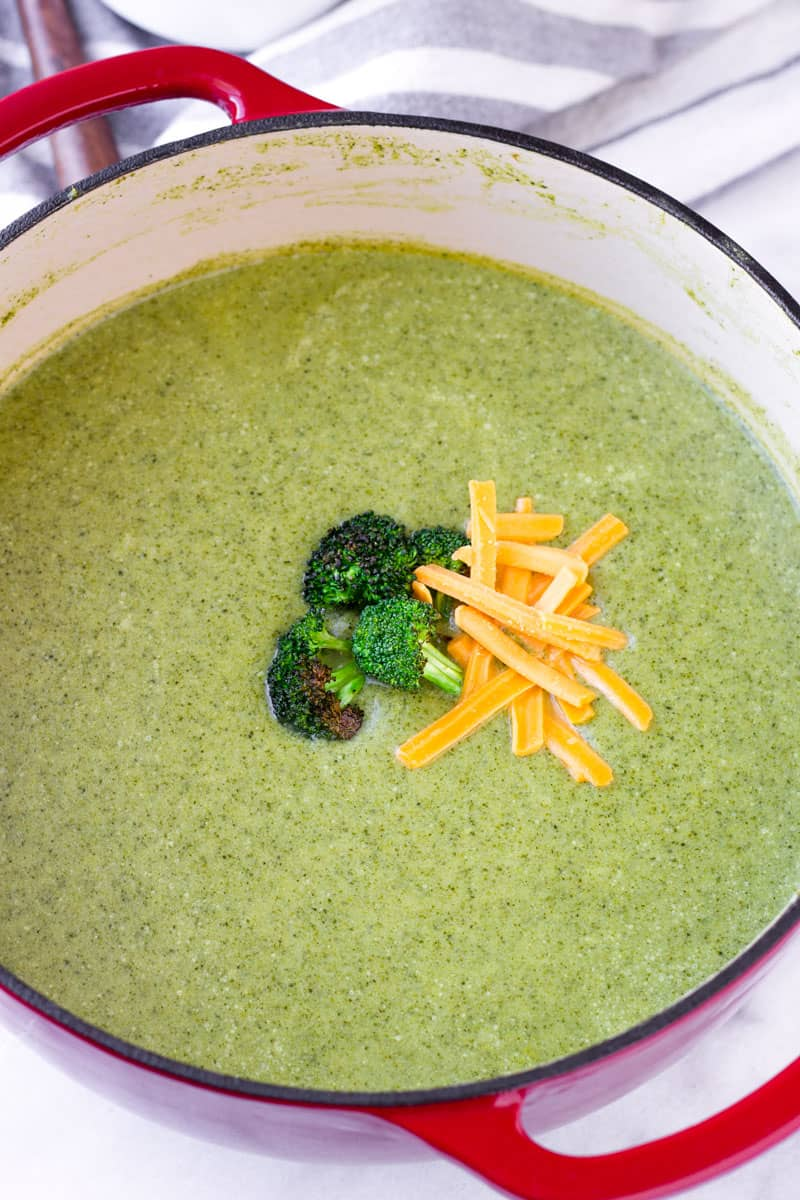Cream of broccoli soup with cheese garnish in a red cast iron Dutch oven