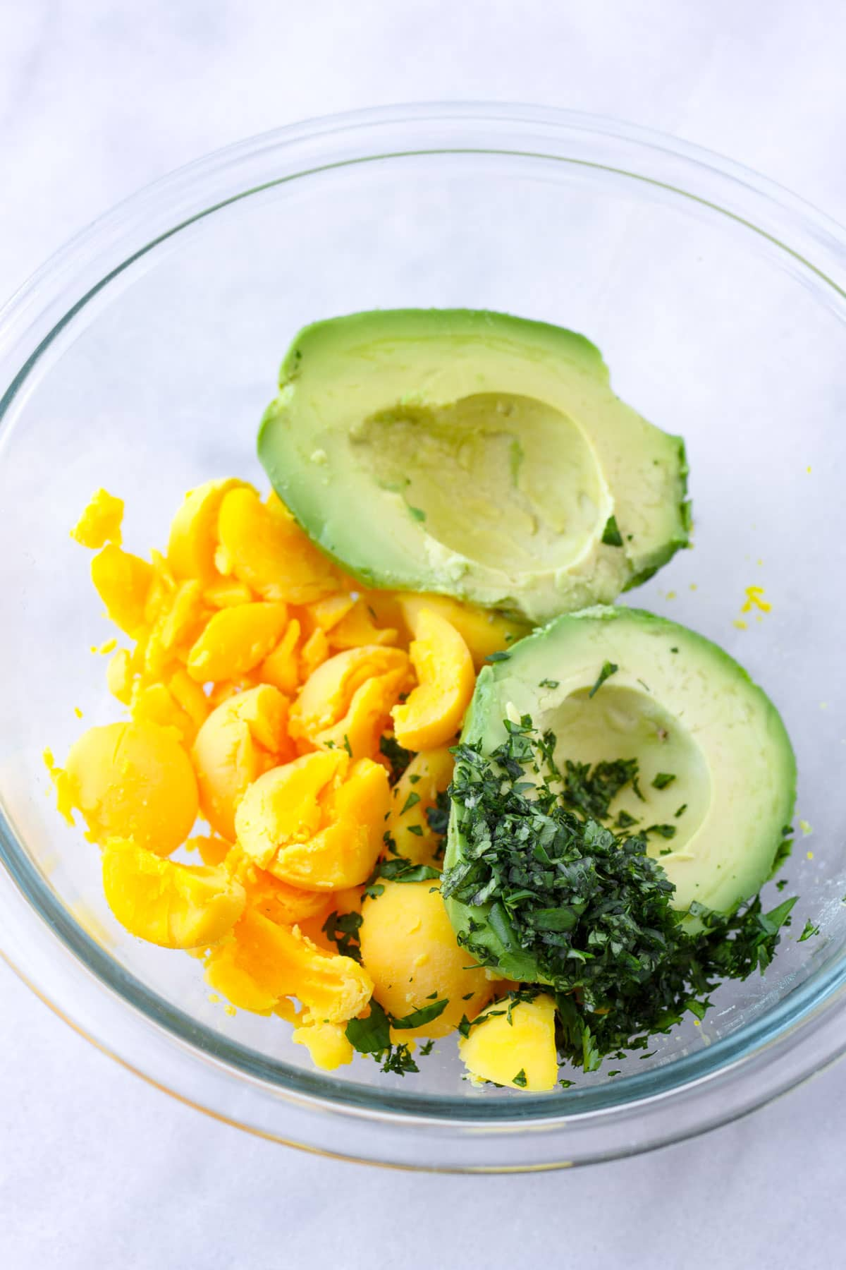 a glass bowl with egg yolks, avocado and chopped cilantro
