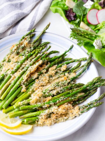 roasted asparagus with breadcrumbs on a plate with a salad in the back