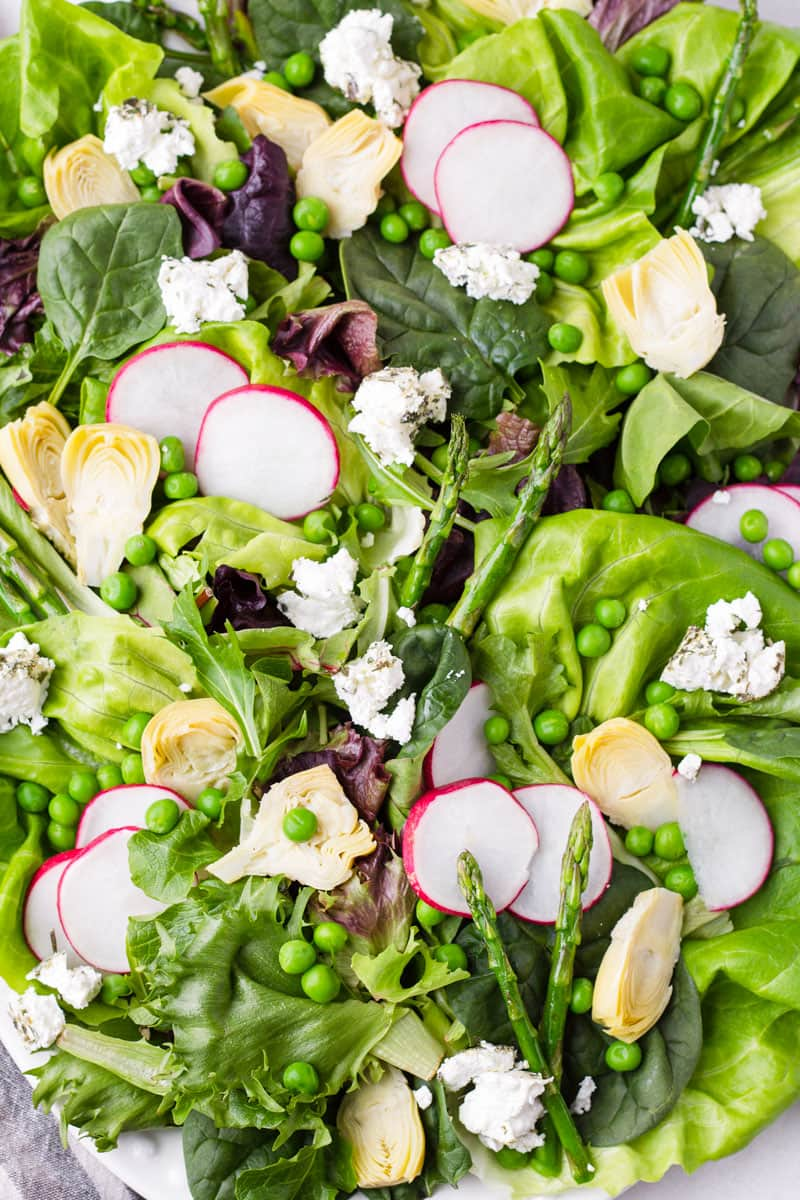 close up view of green spring pea and asparagus salad platter