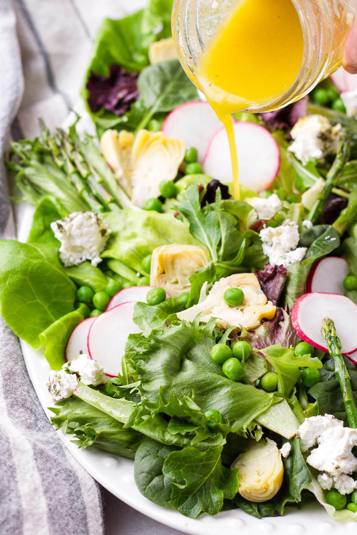 lemon dressing in a jar being poured onto a platter of seasonal greens salad