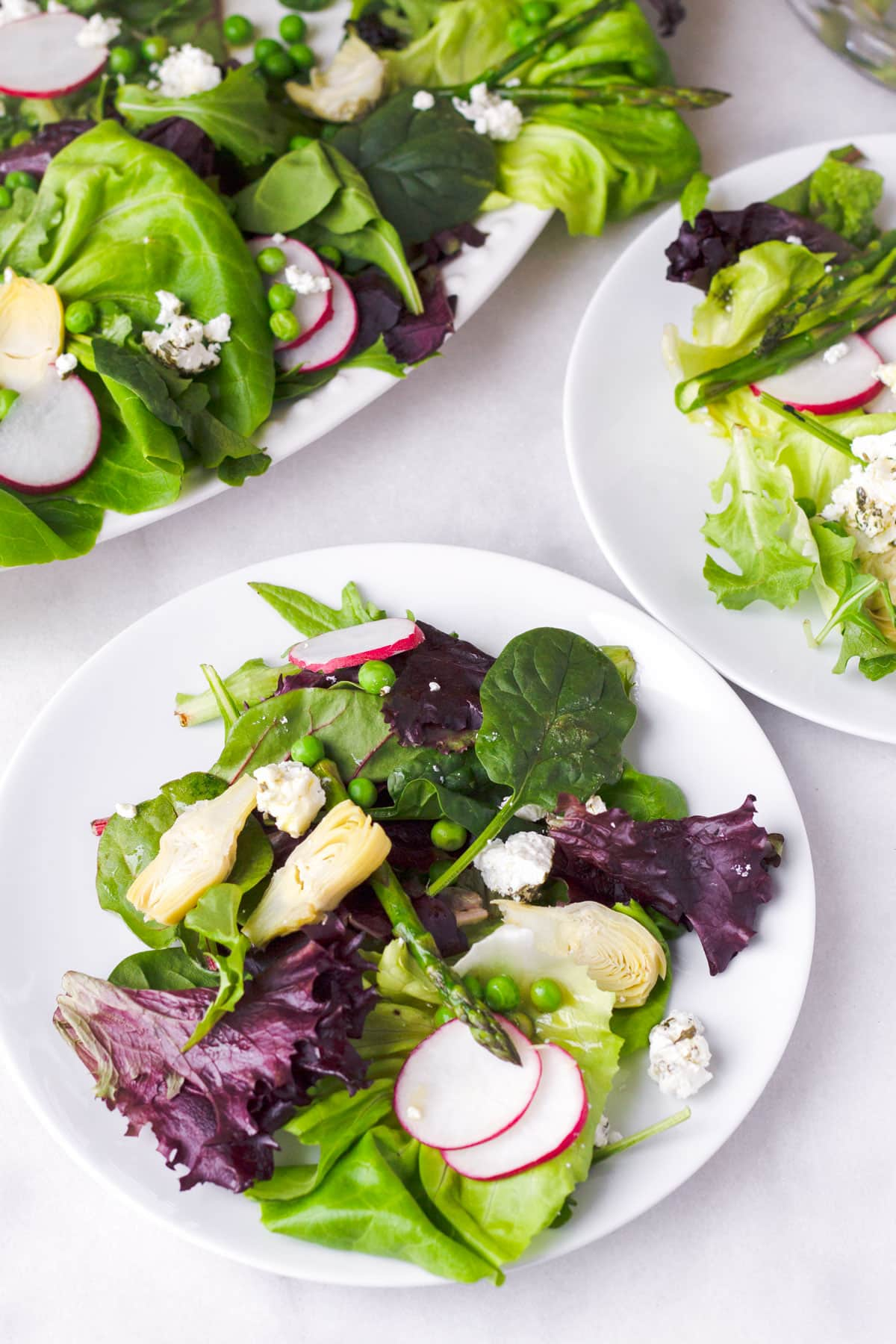 Two individual portions of mixed green salad next to a bigger platter of salad