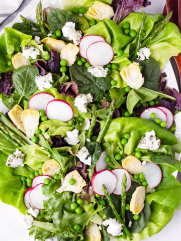 top view of fresh salad with asparagus, peas, lettuce, radishes, artichokes, and greens