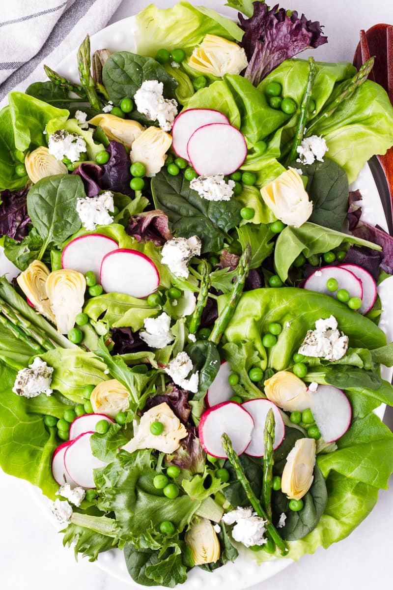 top view of fresh spring salad made with peas, greens, and asparagus