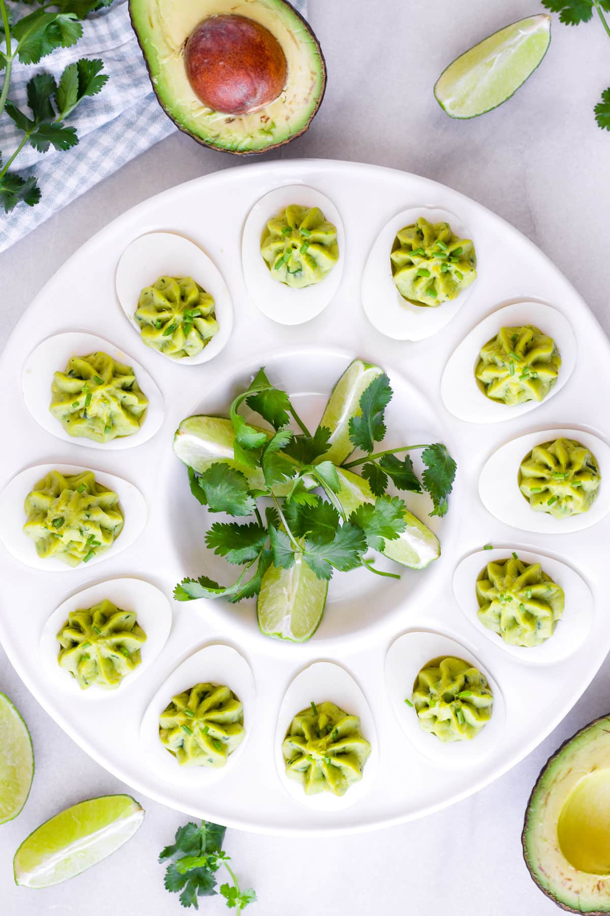 a round plate with twelve deviled eggs and limes with cilantro in the middle
