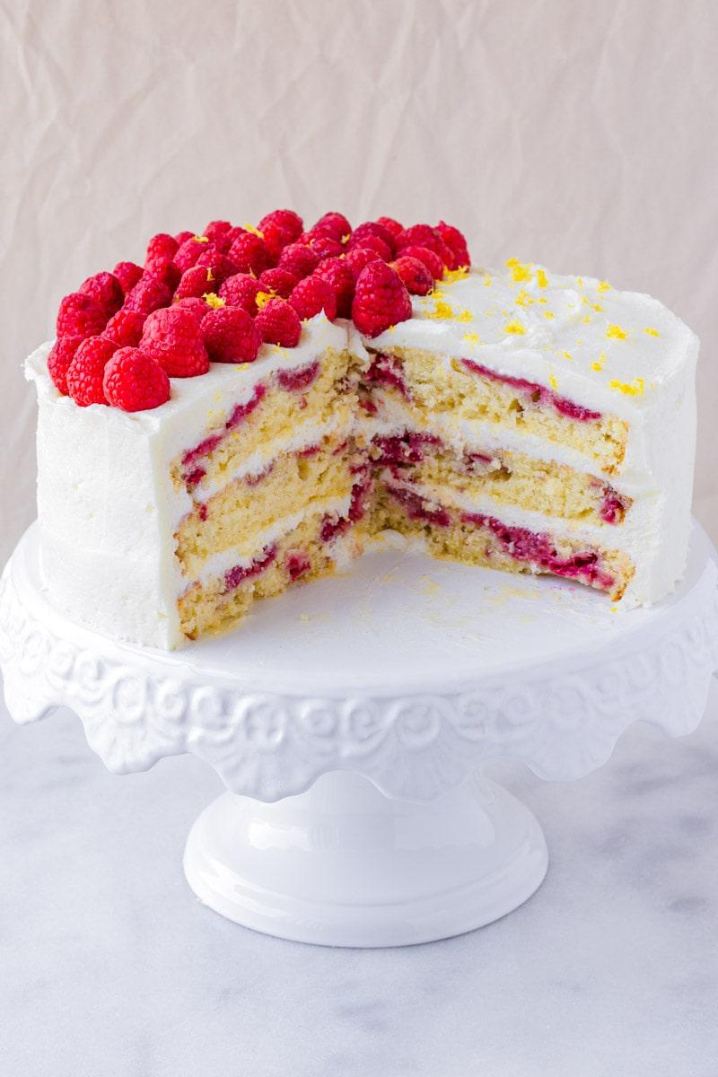 the inside of a lemon raspberry lemon cake with fresh raspberries on top
