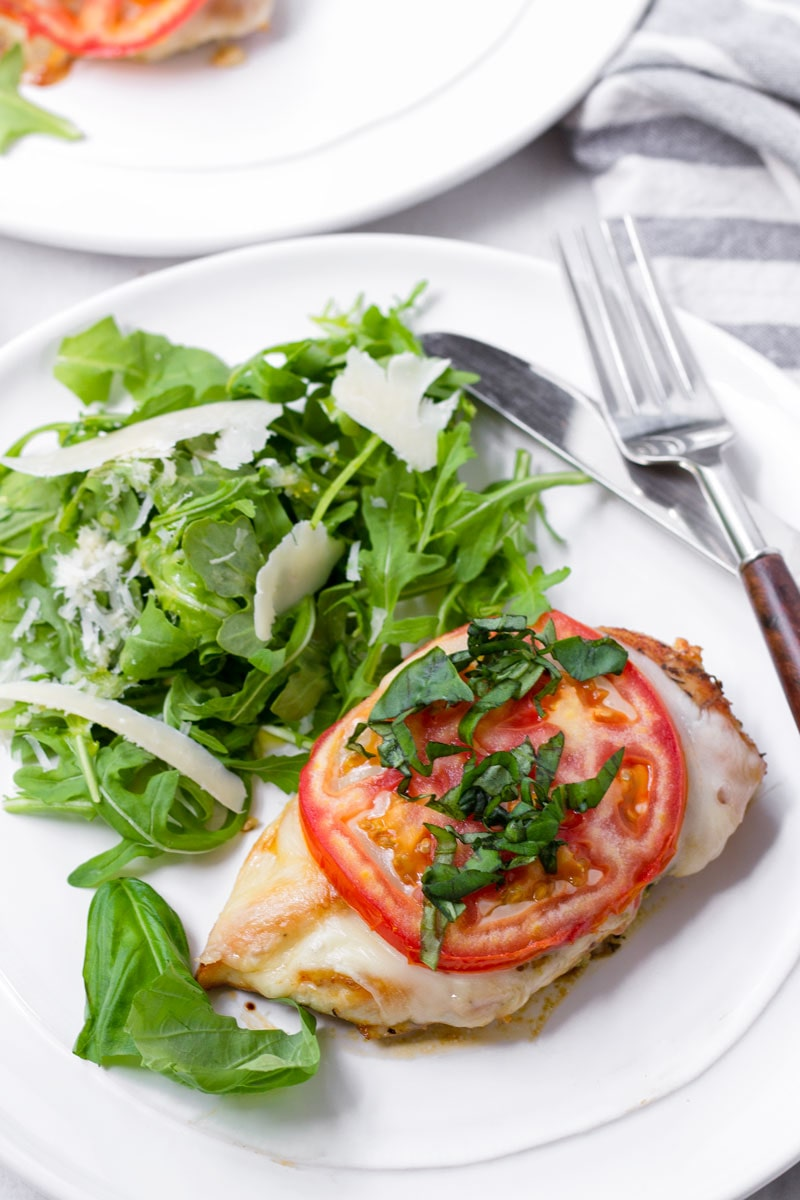 one serving of chicken margherita with a side salad on a round plate and a fork