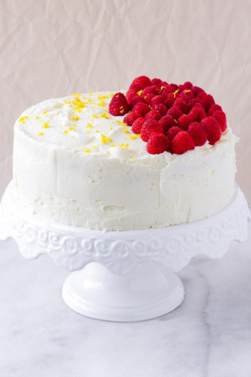 Decorated cake with buttercream frosting and topped with raspberries and lemon zest
