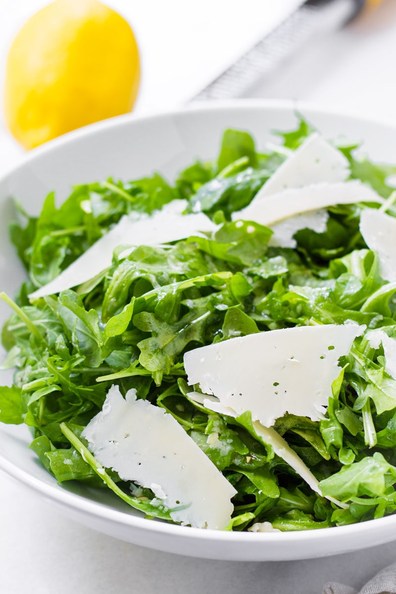Salad with simple lemon and olive oil dressing, with lemon and zester in the back