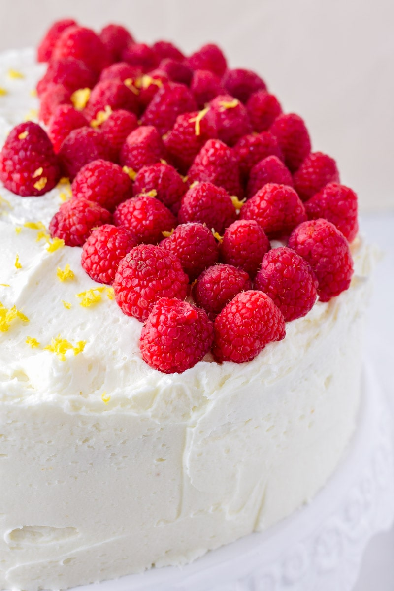 lots of raspberries arranged on a decorated cake