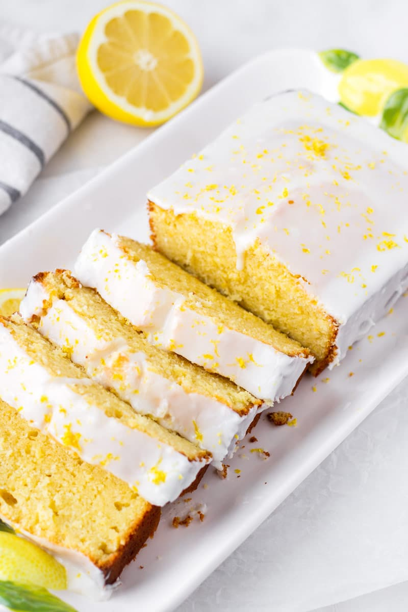 a sliced 9 by 5 loaf of lemon cake on a rectangular plate