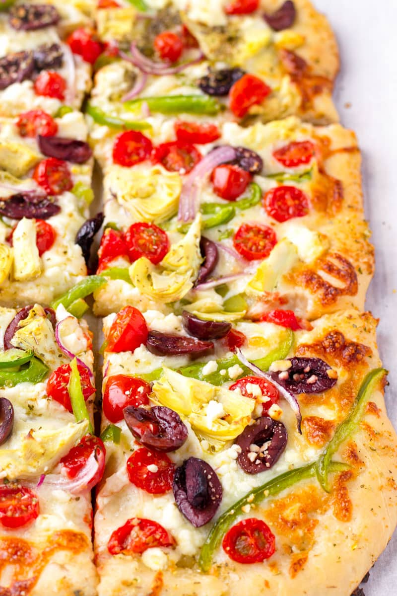 greek style pizza with feta, olives, artichokes, and more