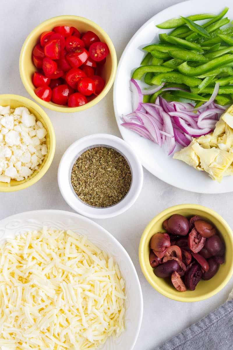 small yellow and white bowls with pizza ingredients