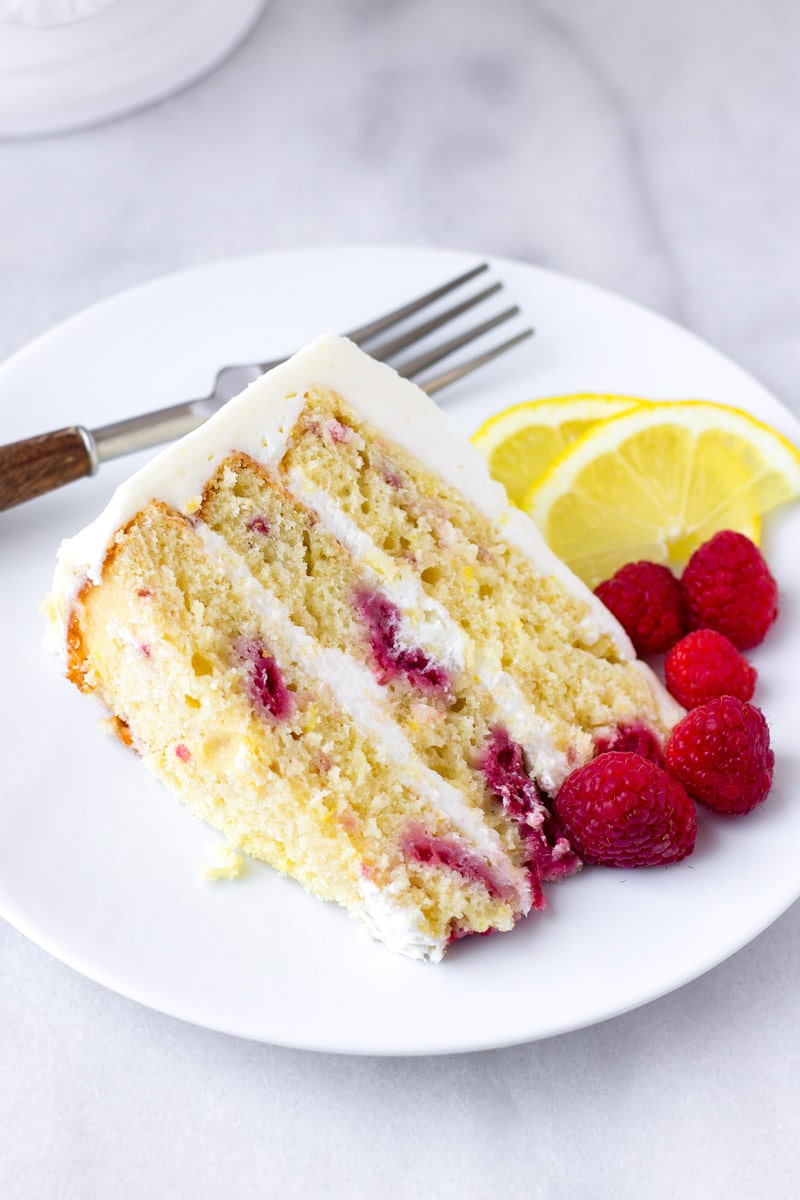 A slice of lemon raspberry cake on a plate with a fork
