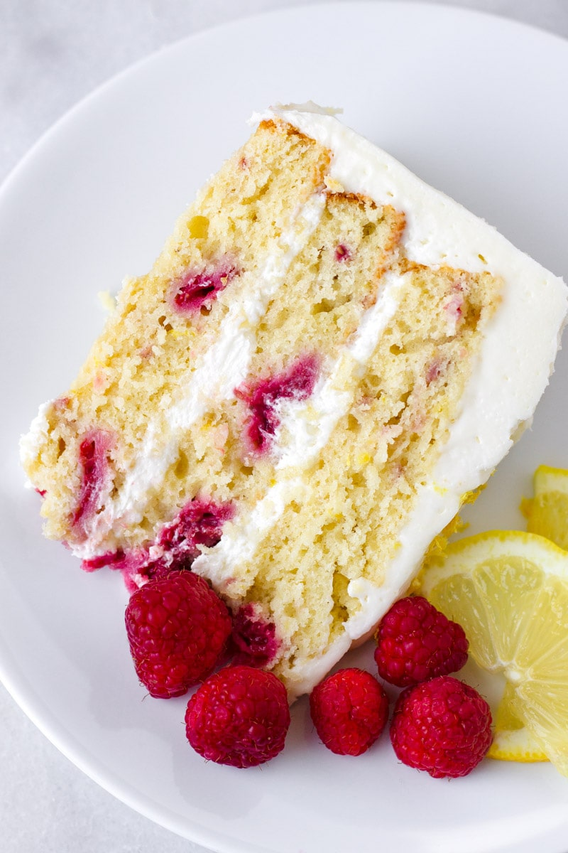An individual slice of layer lemon cake with fresh raspberries