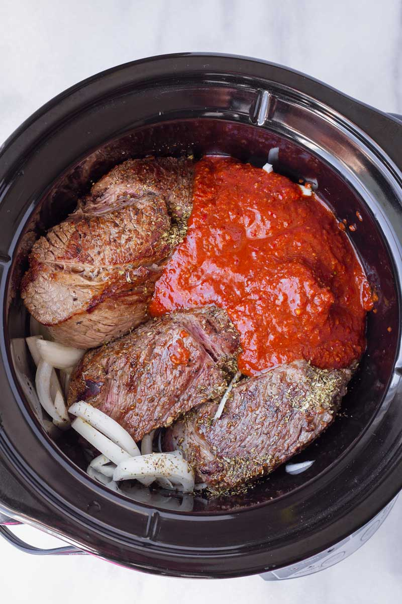 seared beef with marinade and onions in a large slow cooker
